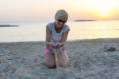 Blond woman plays with the sand Royalty Free Stock Photography