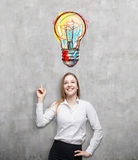 Blond woman pointing at large colorful light bulb. Portrait of smiling blond businesswoman pointing at large light bulb sketch on concrete wall above her head royalty free stock image