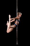 Blond woman during pole dance show exercise Stock Photo