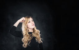 Blond woman pondering over something. Royalty Free Stock Image