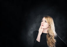 Blond woman pondering over something. Stock Photo