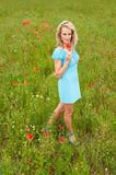 Blond woman in poppy field Royalty Free Stock Photography