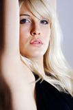 Blond Woman Portrait. Portrait of a serious blond woman with blue eyes, taken in profile with her face turned toward the camera.  Her right arm, closest to the Stock Photo