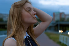 Blond woman portrait on street. Girl looking up at cloudy sky. a Stock Photography