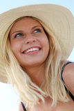 Blond woman portrait in summer. Closeup of beautiful blond woman wearing hat at the beach Stock Photo