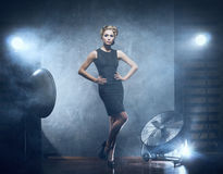 A blond woman posing in a blue dress Stock Image