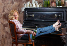 Blond woman posing near retro piano with waxed wine bottle Stock Photos