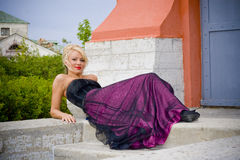 Blond woman posing outdoors. Attractive young blond woman posing outdoors wearing purple dress Stock Photos