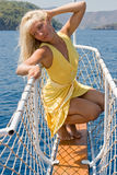 Blond woman posing on the ship's bow. #4. Blond woman in yellow posing on the ship's bow. #4 stock images
