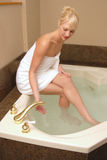 Blond woman preparing bath Stock Photos