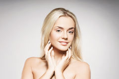 Blond woman with pure skin posing on grey background Royalty Free Stock Images