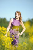 Blond woman in a purple dress Royalty Free Stock Image