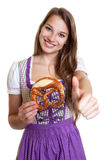 Blond woman in purple dress with pretzel showing thumb Royalty Free Stock Photo