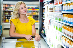 Blond woman pushing cart choosing products Royalty Free Stock Images