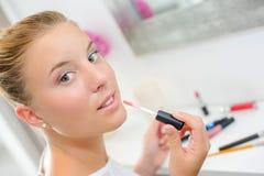 Blond woman putting on lip gloss Stock Photo