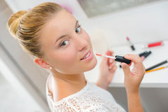 Blond woman putting on lip gloss Royalty Free Stock Photos