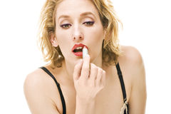 Blond woman putting red lipstick makeup Stock Photos