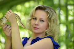 Blond woman  with a python in hands Stock Image
