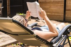 Blond woman reading book by taking sunbath in the house backyard. Blond woman reading a book and taking sunbath in the backyard at summer time stock images