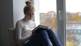 Blond woman reading book stock footage