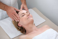 Blond woman receiving massage Stock Images