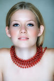 Blond woman with red beads Royalty Free Stock Photos