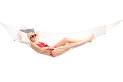 Blond woman in red bikini lying in a hammock. Blond woman in red bikini costume lying in a hammock and relaxing isolated on white background Stock Photos