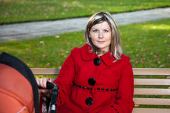 Blond woman in red coat holding handle or pram. Royalty Free Stock Photography