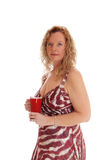 Blond woman with red coffee mug. A image of a blond woman in a summer dress standing in profile holding Royalty Free Stock Images