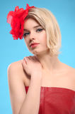 Blond woman with a red flower in hair Stock Photos