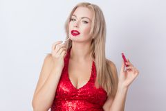 Blond woman with red lipgloss. Photo of cute blonde woman in bright red dress. Holding red lipgloss in hands royalty free stock photos