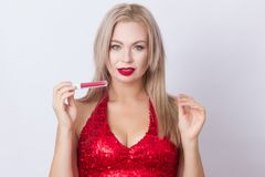 Blond woman with red lipgloss. Photo of cute blonde woman in bright red dress. Holding red lipgloss in hands royalty free stock photo