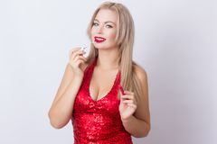 Blond woman with red lipgloss. Photo of cute blonde woman in bright red dress. Holding red lipgloss in hands stock photo