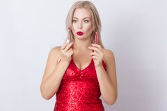 Blond woman with red lipgloss. Photo of cute blonde woman in bright red dress. Holding red lipgloss in hands stock photography