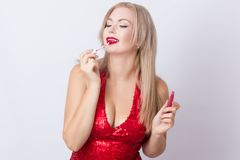 Blond woman with red lipgloss. Photo of cute blonde woman in bright red dress. Holding red lipgloss in hands stock image