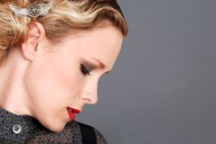 Blond woman with red lipstick side profile. Headshot of a blond woman with red lipstick side profile on gray background royalty free stock images