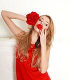 Blond woman with red rose in studio, girl and flower. Beauty and love concept Royalty Free Stock Photography