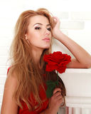 Blond woman with red rose in studio, girl and flower. Beauty and love concept Stock Photos