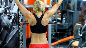 The blond woman with red shorts and black top exercises on the gym equipment stock footage