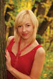 Blond woman  in red is by a tree Royalty Free Stock Photo