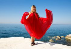 Blond woman in the red. Woman in the red dress on the white stone at the beach in Cyprus Stock Photography
