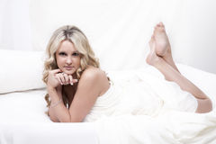 Blond woman relaxing on bed Royalty Free Stock Photos