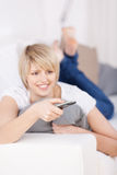 Blond woman with remote control Stock Photo