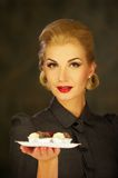 Blond woman in retro dress with plate of sweets Stock Photos
