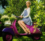 Blond woman on a retro roller Royalty Free Stock Images