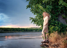 Blond woman on the river bank Royalty Free Stock Images