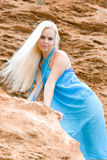 Blond woman among rocks Stock Images