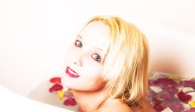Blond woman in rose petal bath Stock Photo