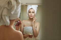 Blond woman rubbing gently a cream Stock Photo