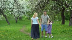 Blond woman running toward her loving family man, girl and boy. Happy people spend time in spring garden. Beautiful blooming white tree park. Static shot stock video footage